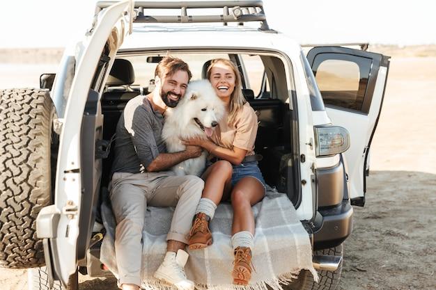 Schönes junges glückliches paar sitzt hinten in ihrem auto am strand und spielt mit hund