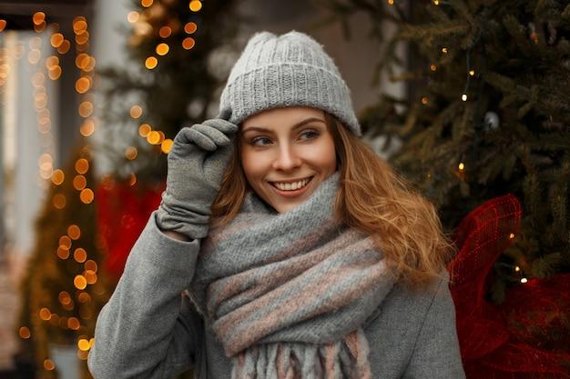 Schönes junges glückliches stilvolles mädchen mit einem erstaunlichen lächeln in modischer strickkleidung mit einer strickmütze und einem stilvollen schal auf der straße nahe den lichtern in den winterferien