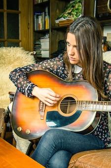 Schönes junges hippie-mädchen, das akustische gitarre spielt, die zu hause auf einem sofa sitzt. retro-vintage-farben-edition