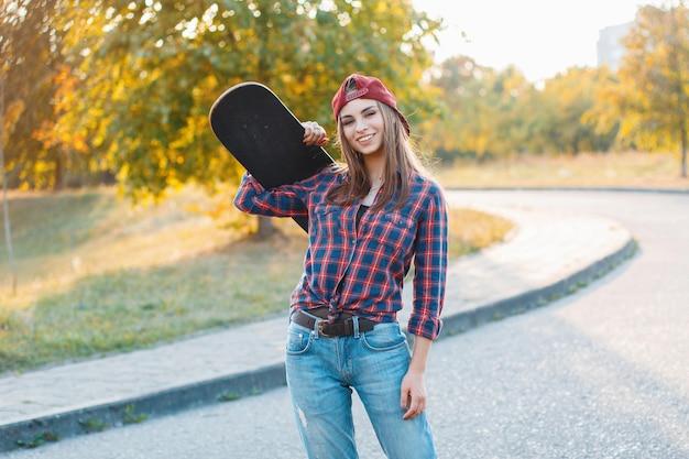 Schönes junges hipster-mädchen in stilvollen kleidern, die ein skateboard halten und bei sonnenuntergang lächeln