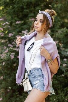 Schönes junges hipster-mädchen mit bandana in trendiger freizeitkleidung: lila sweatshirt, zerrissene jeans-shorts und weißes t-shirt mit handtasche und damenaccessoires im freien
