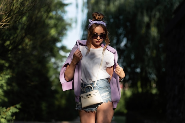 Schönes junges hipster-mädchen mit vintage-bandana und sonnenbrille in modischen denim-shorts und weißem t-shirt mit violettem kapuzenpulli spaziergang in der natur