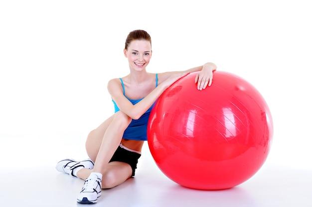 Schönes junges hübsches mädchen mit rotem fitball - lokalisiert