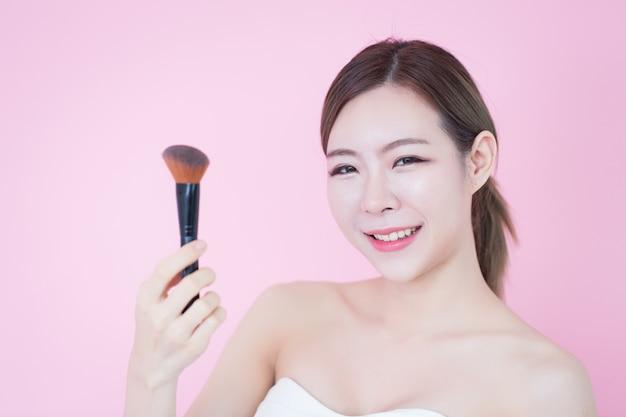 Schönes junges kaukasisches asiatisches frauenlächeln, das natürliches make-up des kosmetischen bürstenpulvers anwendet. kosmetologie, hautpflege, gesichtsreinigung