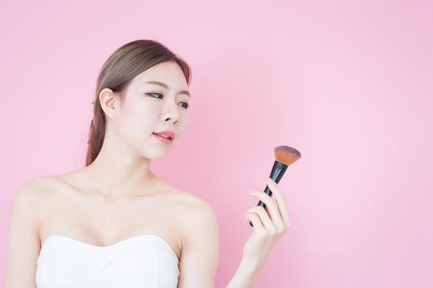 Schönes junges kaukasisches asiatisches frauenlächeln, das natürliches make-up des kosmetischen bürstenpulvers anwendet.