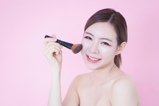 Schönes junges kaukasisches asiatisches frauenlächeln, das natürliches make-up des kosmetischen bürstenpulvers anwendet