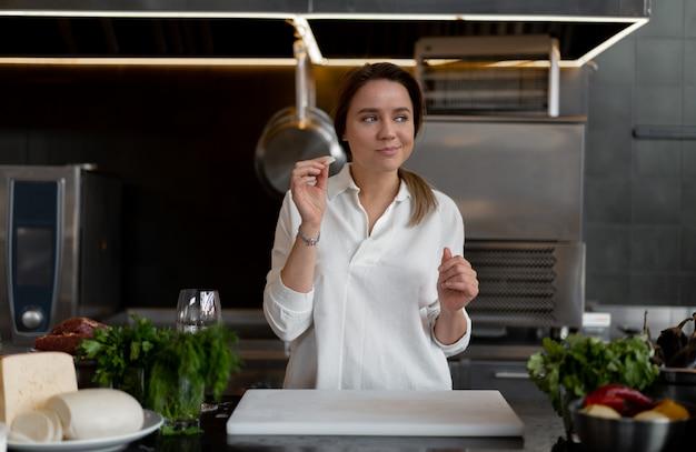 Schönes junges kaukasisches mädchen, das in der küche in einer weißen uniform steht, die ein stück käse lächelt und schmeckt. nette frau 30s jahre alt im weißen hemd mit lebensmittelbestandteilen käsefleischgemüse.