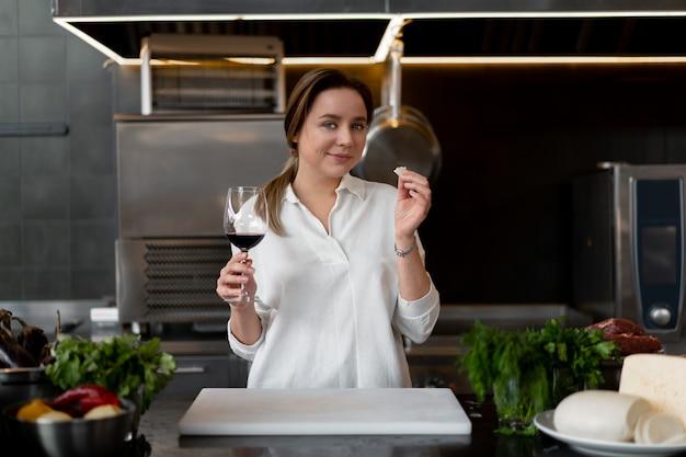 Schönes junges kaukasisches mädchen, das in der küche in einer weißen uniform steht, die rotwein lächelt und schmeckt nette frau 30s jahre alt im weißen hemd mit lebensmittelbestandteilen käsefleischgemüse trinken