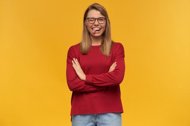 Schönes junges lächelndes blondes junges mädchen, das glücklich zur kamera schaut und roten pullover und eine brille trägt