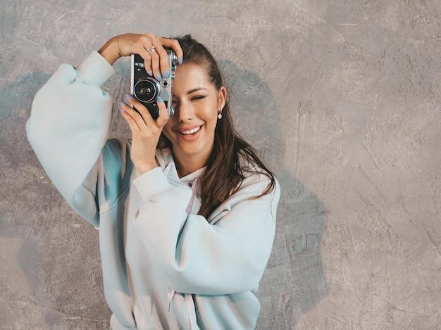 Schönes junges lächelndes fotografmädchen, das fotos unter verwendung ihrer retro- kamera macht. frau, die bilder macht.