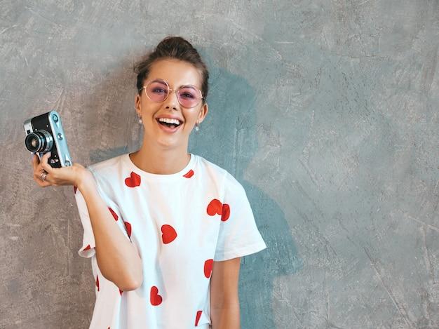 Schönes junges lächelndes fotografmädchen, das fotos unter verwendung ihrer retro- kamera macht.