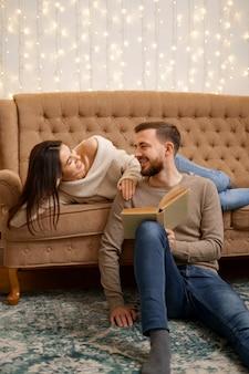 Schönes junges liebendes paar, das aneinander bindet und lächelt, während frau ein buch hält.