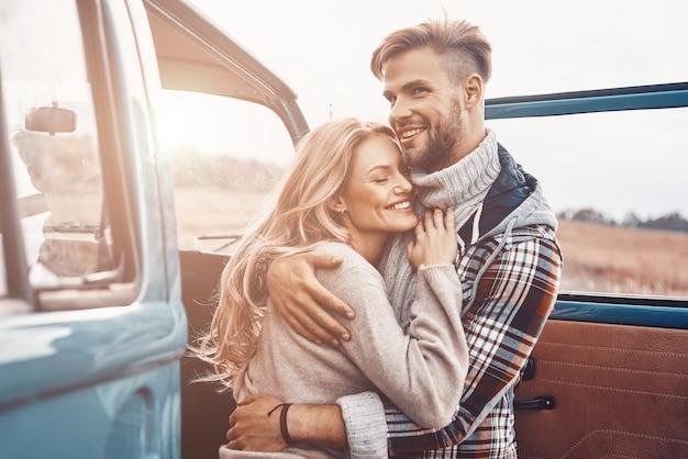Schönes junges liebevolles paar, das sich umarmt, während es im freien in der nähe des minivans steht