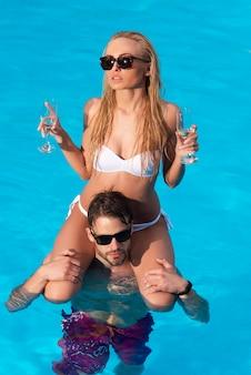Schönes junges mädchen am strand. sexy paar mit champagnerwein im schwimmbad. reise