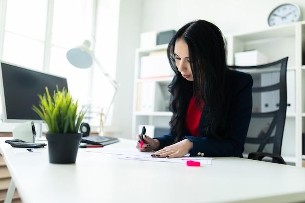 Schönes junges mädchen arbeitet mit dokumenten im büro am tisch. das mädchen hebt wichtige punkte im dokument mit einer rosa markierung hervor.