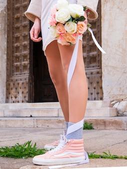 Schönes junges mädchen auf heller kleidung mit einem blumenstrauß von rosenblumen.