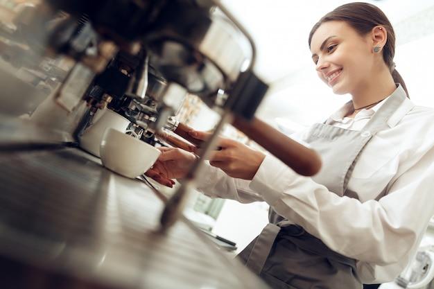 Schönes junges mädchen barista, das kaffee zubereitet