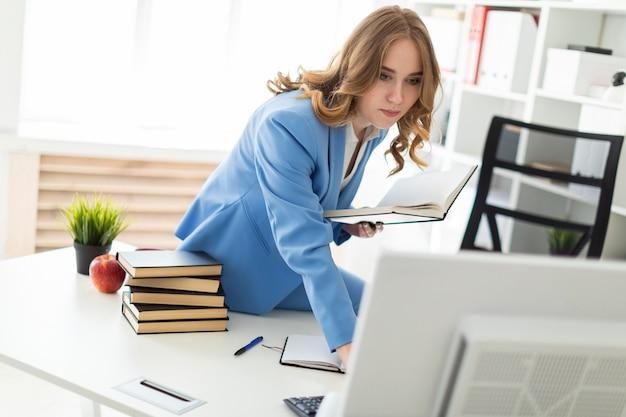 Schönes junges mädchen, das am schreibtisch im büro sitzt, ein buch in ihrer hand hält und den monitor betrachtet.