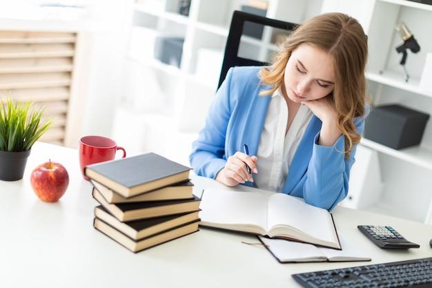 Schönes junges mädchen, das am schreibtisch im büro sitzt, einen stift in ihrer hand hält und ein buch liest.