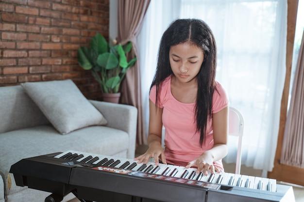 Schönes junges mädchen, das an einem klavierinstrument sitzt