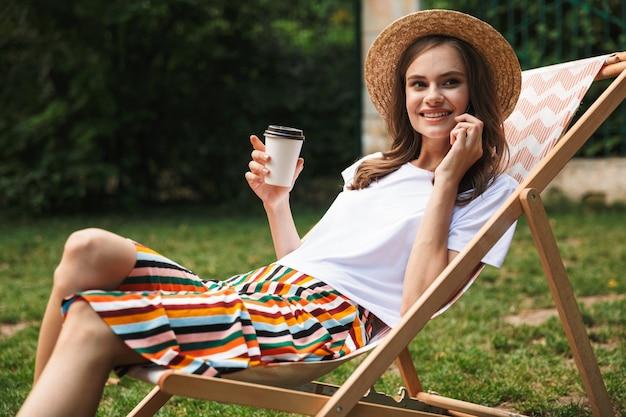 Schönes junges mädchen, das auf einer hängematte im stadtpark draußen im sommer ruht, kaffee zum mitnehmen trinkt und auf handy spricht