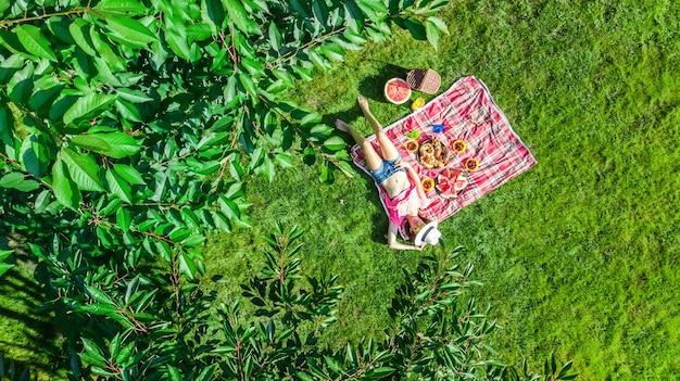 Schönes junges mädchen, das auf gras entspannt, sommerpicknick im park im freien habend