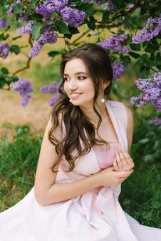 Schönes junges mädchen, das aus den grund im garten mit blühender flieder sitzt. sie ist glücklich und lächelt ein schönes lächeln mit weißen zähnen. schau weg