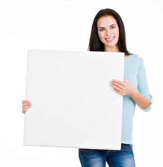 Schönes junges mädchen, das ein plakat lokalisiert auf weiß hält