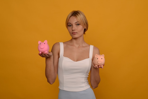 Schönes junges mädchen, das ein sparschwein der zwei schweine auf gelbem hintergrund hält. um geld zu sparen, vermögen und finanzkonzept.