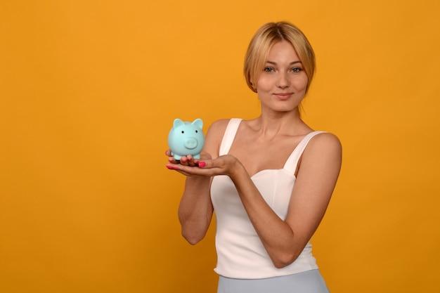 Schönes junges mädchen, das ein sparschwein des schweins auf gelbem hintergrund hält. um geld zu sparen, vermögen und finanzkonzept.