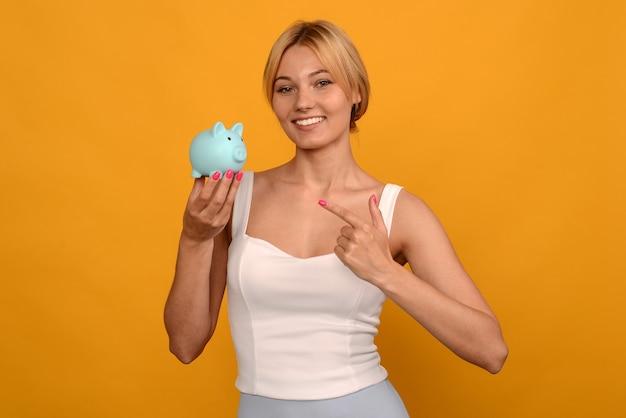 Schönes junges mädchen, das ein sparschwein des schweins hält und finger auf gelbem hintergrund zeigt. um geld zu sparen, vermögen und finanzkonzept. ich