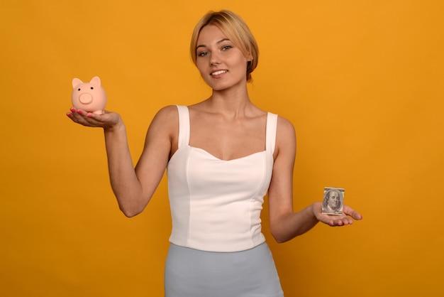 Schönes junges mädchen, das ein sparschwein und ein dollarschwein auf gelbem hintergrund hält. um geld zu sparen, vermögen und finanzkonzept.