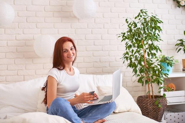 Schönes junges mädchen, das eine bankkarte und einen laptop auf dem bett lächelt und hält.