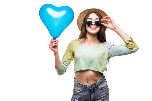 Schönes junges mädchen, das einen luftballon des blauen herzens hält. das konzept des valentinstags