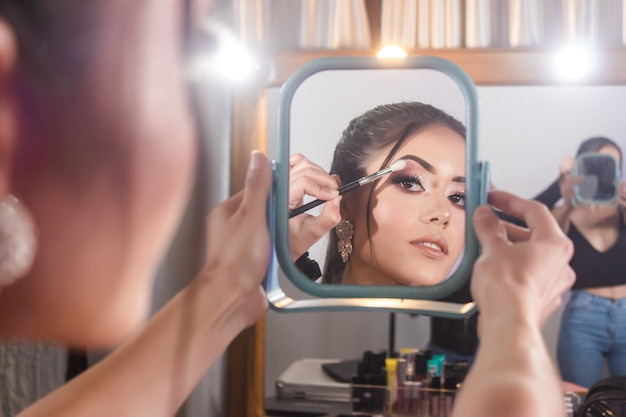 Schönes junges mädchen, das einen spiegel hält, während der maskenbildner schatten auf ihren augen verwischt.