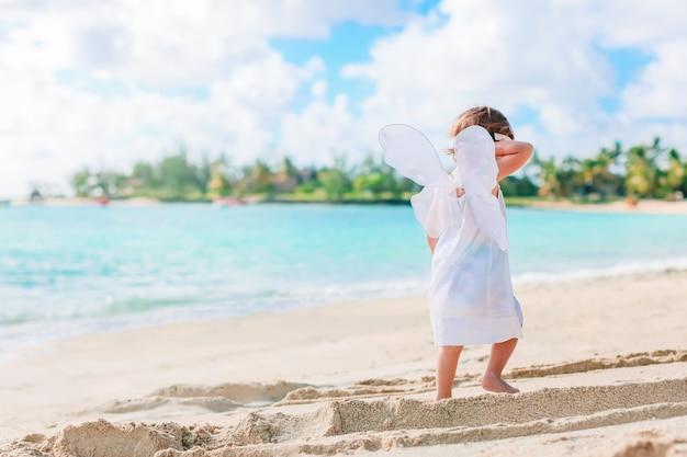 Schönes junges mädchen, das engelsflügel am strand trägt