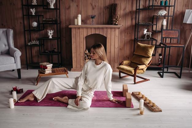 Schönes junges mädchen, das entspannend auf matte mit kerzen im stilvollen gemütlichen komforthauptinnenraum mit bequemen möbeln sitzt.