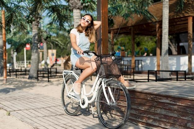 Schönes junges mädchen, das fahrrad draußen reitet