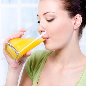 Schönes junges mädchen, das frischen orangensaft trinkt