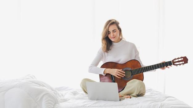 Schönes junges mädchen, das gitarre spielend auf bett im schlafzimmer sitzt