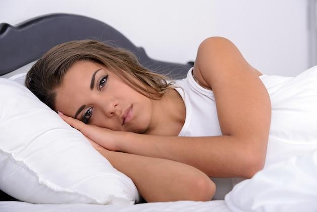 Schönes junges mädchen, das im bett in ihrem schlafzimmer schläft
