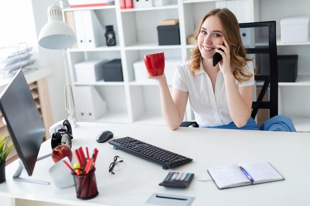 Schönes junges mädchen, das im büro sitzt, einen becher in ihrer hand hält und am telefon spricht.