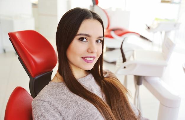 Schönes junges mädchen, das im roten zahnmedizinischen stuhl lächelt