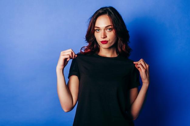 Schönes junges mädchen, das im schwarzen t-shirt im studio auf blau aufwirft