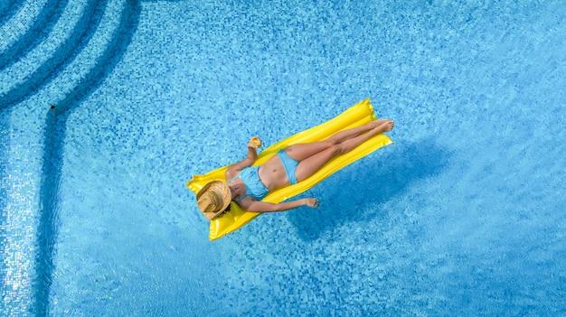 Schönes junges mädchen, das im schwimmbad entspannt, frau schwimmt auf aufblasbarer matratze und hat spaß im wasser im familienurlaub, tropischem ferienort, luftdrohnenansicht von oben