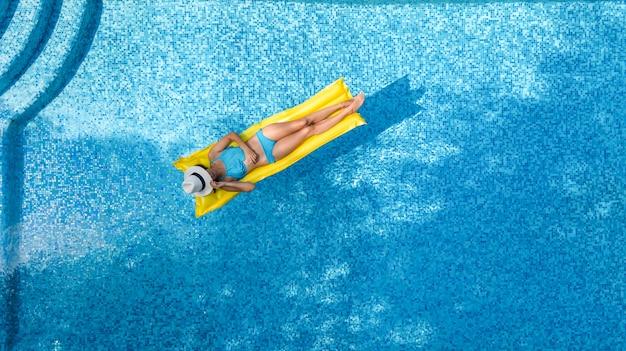 Schönes junges mädchen, das im schwimmbad entspannt, schwimmt auf aufblasbarer matratze und hat spaß im wasser im familienurlaub, tropischem ferienort, luftdrohnenansicht von oben