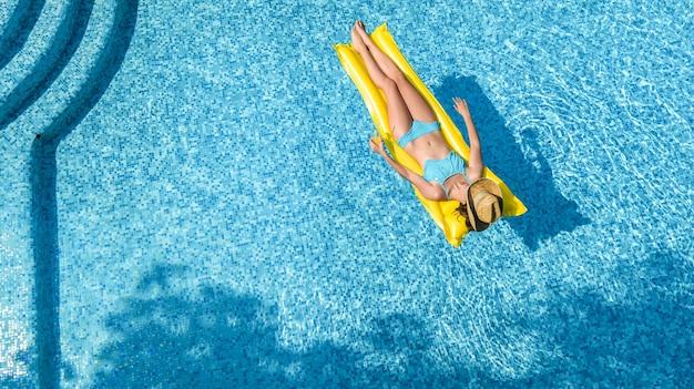 Schönes junges mädchen, das im schwimmbad entspannt