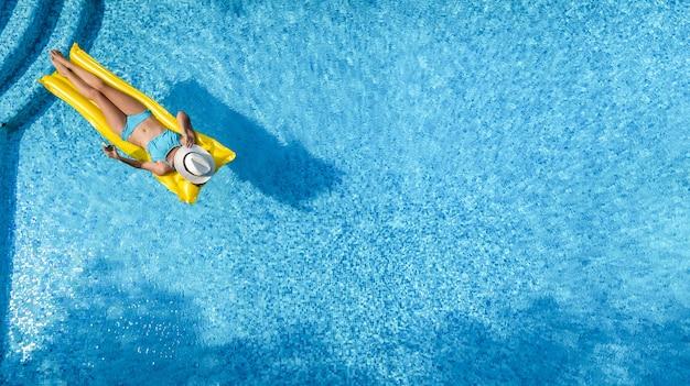 Schönes junges mädchen, das im schwimmbad, frau auf aufblasbarer matratze, luftaufnahme entspannt