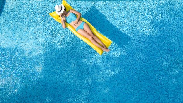 Schönes junges mädchen, das im swimmingpool sich entspannt