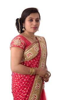 Schönes junges mädchen, das im traditionellen indischen saree auf weißer wand aufwirft.
